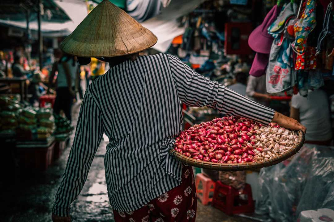 Vietnam market with woman carrying vegetables